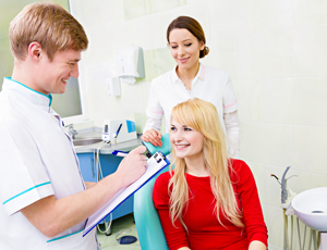 Woman talking to dentist and dental assistant