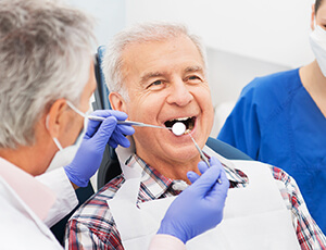 Older male patient receives gum disease screening
