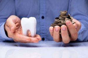 man holding coins and white tooth